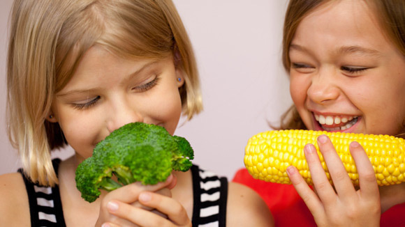 Girls with broccoli and corn-iStockphoto