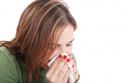 woman with cold blowing Nose