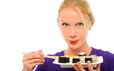 Woman eating tray of sushi